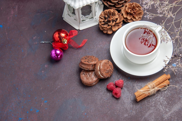 Top view delicious chocolate cookies with cup of tea on dark background pie biscuit sweet cake cookie tea