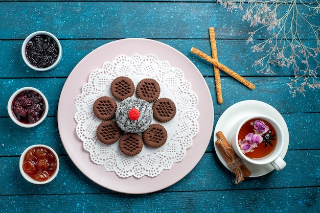 Top view delicious chocolate cookies with jam and cup of tea on a blue rustic desk biscuit tea cookie sweet cake sugar