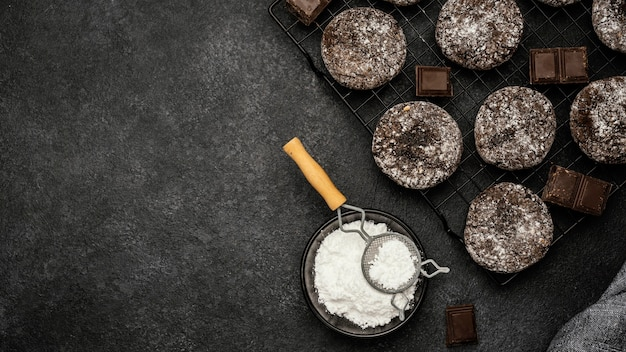 Top view of delicious chocolate cookies with powdered sugar and copy space