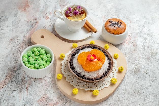 Vista dall'alto delizioso dessert al cioccolato con una tazza di tè sullo sfondo bianco crema biscotto torta frutta dessert