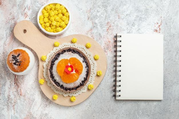 Vista dall'alto delizioso dessert al cioccolato con mandarini a fette su uno sfondo bianco torta alla crema di biscotti alla frutta
