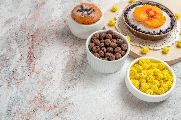 Top view delicious chocolate dessert with tangerines and candies on the white background cream biscuit cake fruit dessert