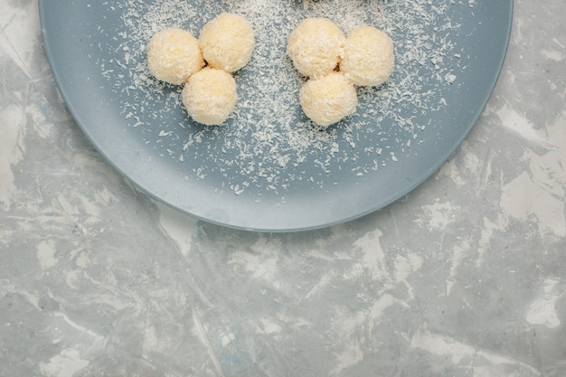 Top view of delicious coconut candies inside blue plate on white desk
