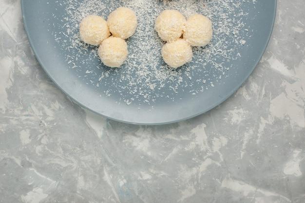 Vista dall'alto di deliziose caramelle al cocco all'interno del piatto blu sulla scrivania bianca
