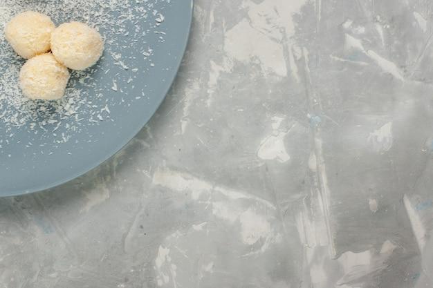 Vista dall'alto di deliziose caramelle al cocco all'interno del piatto blu su superficie bianca