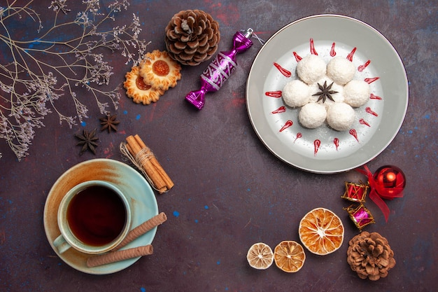 Вид сверху вкусные кокосовые конфеты маленькие и круглые с чашкой чая на темном фоне кокосовые конфеты сладкий торт печенье чай