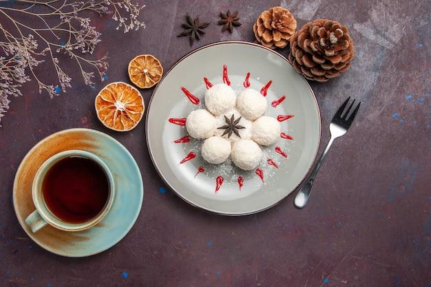Вид сверху вкусные кокосовые конфеты маленькие и круглые, сформированные с чашкой чая на темном фоне, кокосовые конфеты, чай, сладкое печенье, печенье