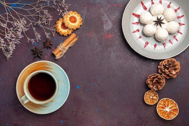 Vista dall'alto deliziose caramelle al cocco piccole e rotonde formate con una tazza di tè su sfondo scuro caramelle al cocco biscotti dolci al tè