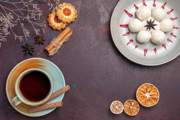 Vista dall'alto deliziose caramelle al cocco piccole e rotonde formate con tè su sfondo scuro caramelle al cocco tè dolce torta biscotto