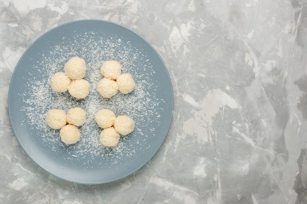 Vista dall'alto di deliziose palline dolci di caramelle al cocco sulla superficie bianca