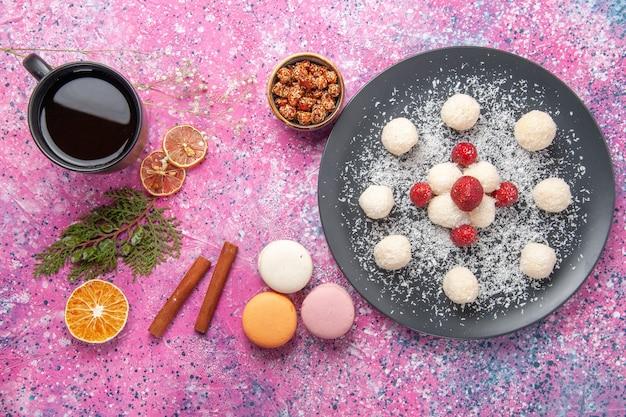 Vista dall'alto di deliziose palline dolci di caramelle al cocco con macarons francesi sulla scrivania rosa