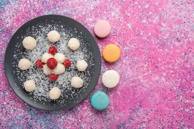 Vista dall'alto di deliziose palline dolci di caramelle al cocco con macarons francesi sulla superficie rosa
