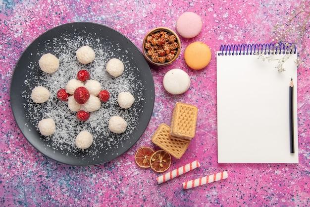 Vista dall'alto di deliziose palline dolci di caramelle al cocco con macarons francesi e cialde sulla scrivania rosa