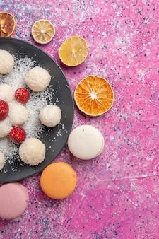 Vista dall'alto di deliziose palline dolci di caramelle al cocco con macarons sulla superficie rosa chiaro
