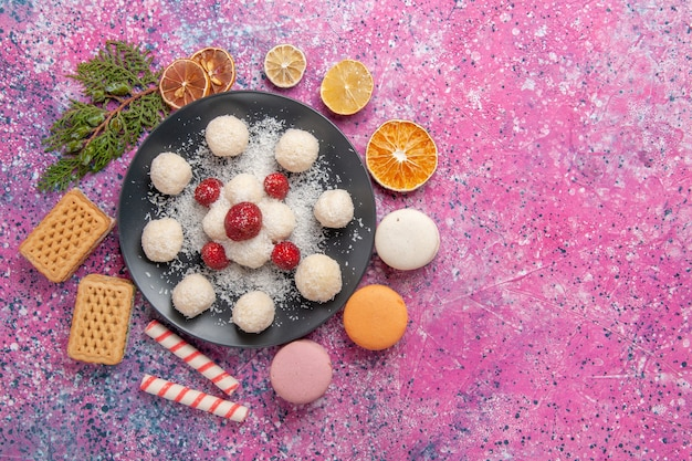 Top view of delicious coconut candies sweet balls with macarons on light pink surface