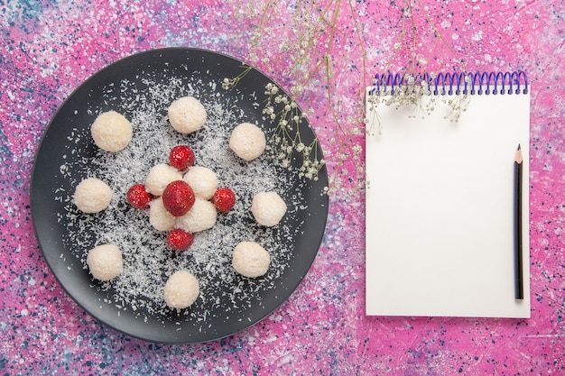 Vista dall'alto di deliziose palline dolci di caramelle al cocco con blocco note sulla superficie rosa