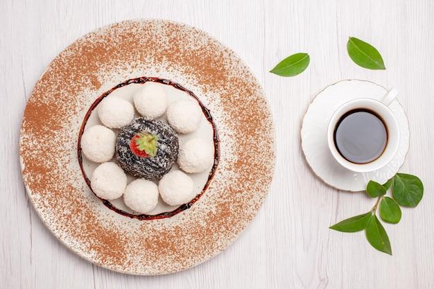 Вид сверху вкусные кокосовые конфеты с шоколадным тортом и чашкой чая на белом фоне чайный торт бисквитные конфеты печенье сладкое