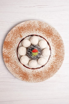 Vista dall'alto deliziose caramelle al cocco con torta al cioccolato su una torta bianca da scrivania biscotto dolce biscotto caramelle