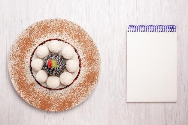 Vista dall'alto deliziose caramelle al cocco con torta al cioccolato su biscotti da scrivania bianchi biscotti dolci caramelle
