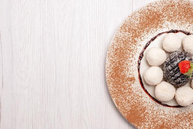 Vista dall'alto deliziose caramelle al cocco con torta al cioccolato su scrivania bianca torta di zucchero biscotto dolce biscotto di caramelle