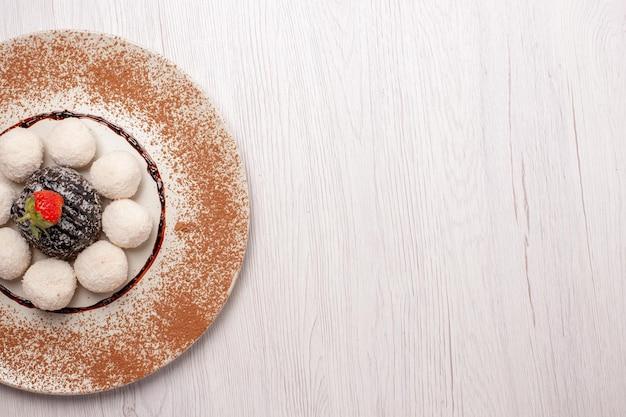 Vista dall'alto deliziose caramelle al cocco con torta al cioccolato sulla scrivania bianca torta di zucchero biscotto biscotti dolci caramelle