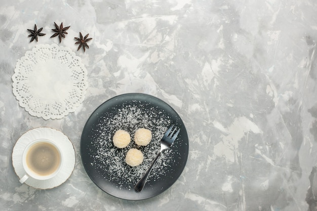 Top view of delicious coconut candies with coffee on white surface