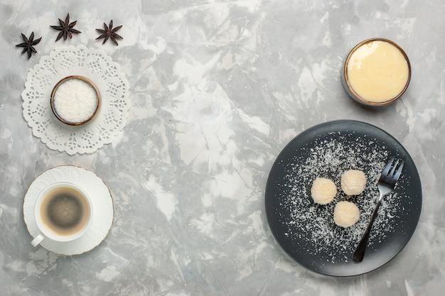Vista dall'alto di deliziose caramelle al cocco con una tazza di caffè sulla superficie bianca