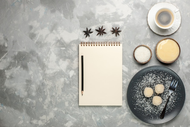 Top view of delicious coconut candies with cup of coffee on white surface