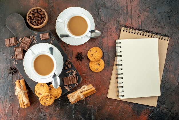 Top view of delicious coffee in white cups on wooden cutting board cookies cinnamon limes chocolate bars spiral notebooks