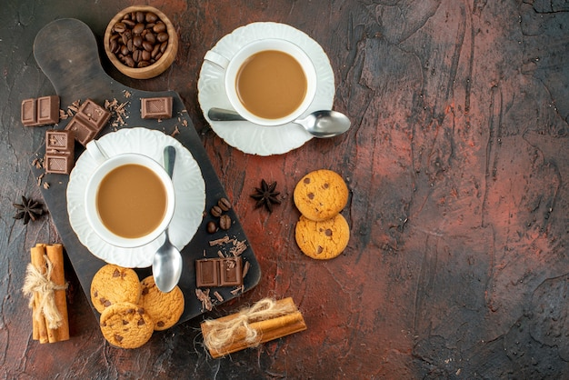 Top view of delicious coffee in white cups on wooden cutting board cookies cinnamon limes chocolate bars