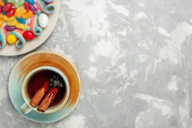Vista dall'alto di deliziose caramelle colorate con marmellata e tazza di tè sulla superficie bianca