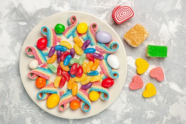 Vista dall'alto di deliziose caramelle colorate con marmellata sulla superficie bianca