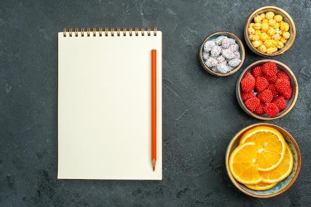 Vista dall'alto deliziose confetture con fette d'arancia e blocco note su superficie scura confettura di frutta caramelle di zucchero goodie
