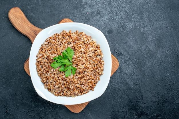 Vista dall'alto delizioso grano saraceno cotto sul pavimento grigio cena pranzo pasto cibo verdure