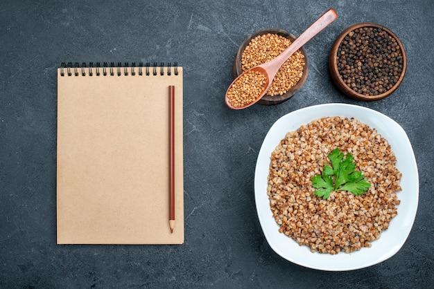 Vista dall'alto delizioso grano saraceno cotto all'interno del piatto su uno spazio grigio scuro