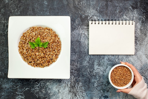 Top view delicious cooked buckwheat inside plate on a light-grey background calorie meal color photo dish bean food
