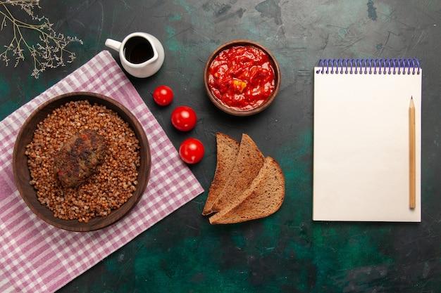 Vista dall'alto delizioso grano saraceno cotto con pagnotte di pane e cotoletta sul piatto di verdure cibo pasto ingrediente superficie verde scuro