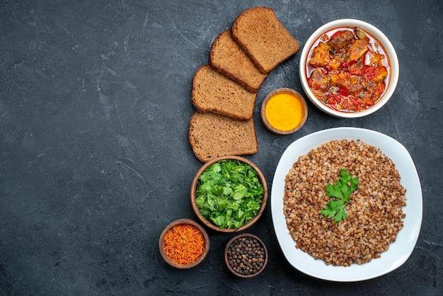Vista dall'alto delizioso grano saraceno cotto con pane e zuppa su uno spazio buio