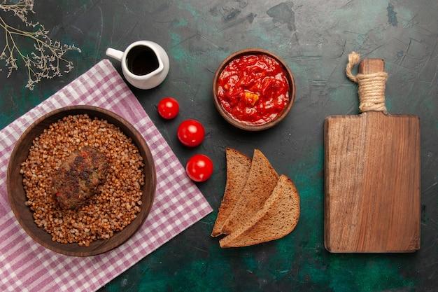 Vista dall'alto delizioso grano saraceno cotto con pagnotte di pane scuro e cotoletta sulla superficie verde scuro ingrediente pasto cibo piatto di verdure