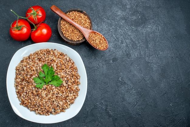 Vista dall'alto delizioso grano saraceno cotto con pomodori freschi su spazio grigio scuro