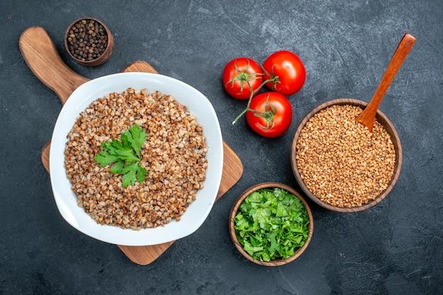 Vista dall'alto delizioso grano saraceno cotto con pomodori freschi e verdure sullo spazio grigio