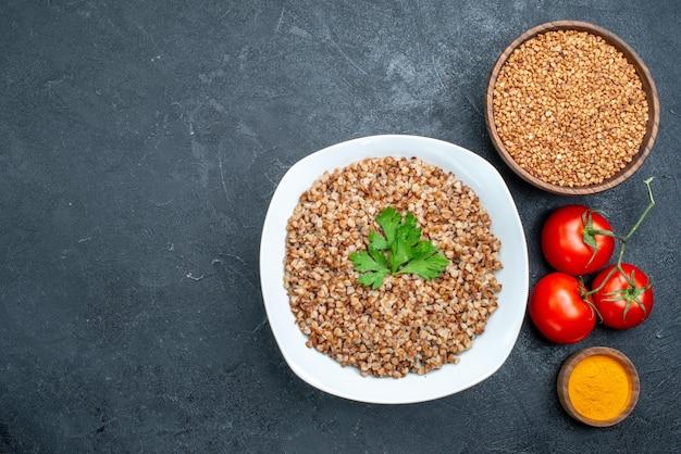 Vista dall'alto delizioso grano saraceno cotto con pomodori freschi su spazio grigio