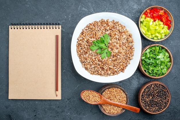 Vista dall'alto delizioso grano saraceno cotto con verdure sulla scrivania grigia