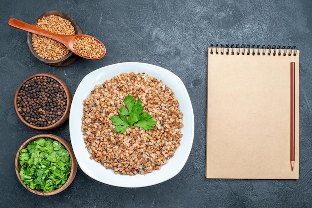 Vista dall'alto delizioso grano saraceno cotto con verdure sullo spazio grigio