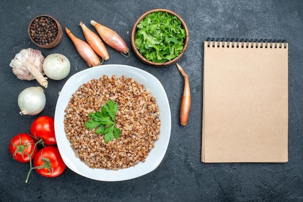 Vista dall'alto delizioso grano saraceno cotto con pomodori e verdure sulla scrivania grigia