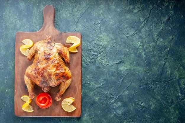 Вид сверху вкусной приготовленной курицы с ломтиками лимона на темно-синей поверхности