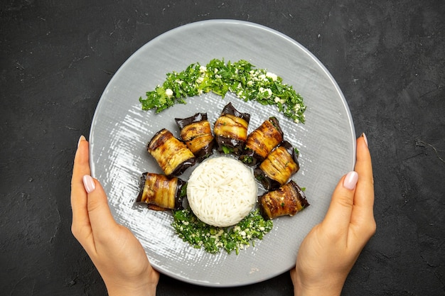 Vista dall'alto deliziose melanzane cotte con riso sulla superficie scura cena cibo olio da cucina farina di riso