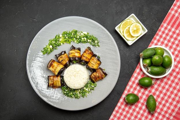 Vista dall'alto deliziose melanzane cotte con riso e feijoa su superficie scura cena cibo che cucina farina di riso