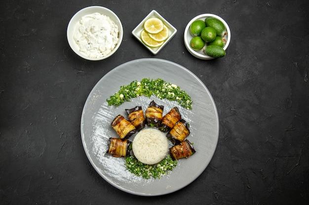 어두운 표면 저녁 식사 음식 요리 기름 쌀 식사에 쌀 레몬과 feijoa와 상위 뷰 맛있는 요리 가지