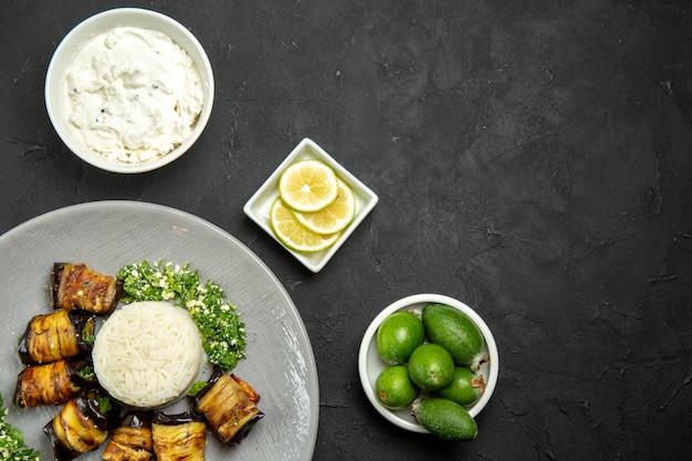 Вид сверху вкусные вареные баклажаны с рисом, лимоном и фейхоа на темной поверхности обеденная еда растительное масло рисовая мука